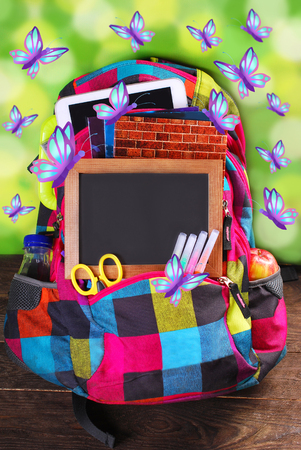end of summer: colorful backpack with various school equipment and flying butterflies as summer holidays concept Stock Photo