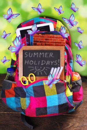 vacanza: zaino colorato con materiale scolastico Vaus e farfalle che volano come le vacanze estive concetto