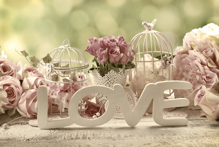 romantic vintage love background with bunches of roses, old cages and and wooden word