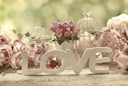 romantische vintage liefde achtergrond met bossen van rozen, oude kooien en en houten woord Stockfoto