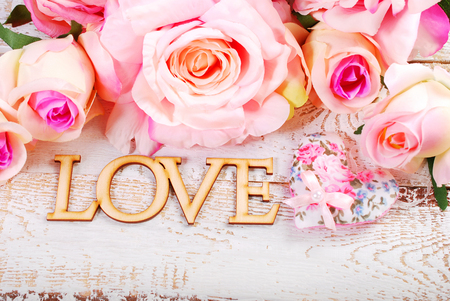romantic love: romantic background with LOVE and roses on old wooden planks Stock Photo