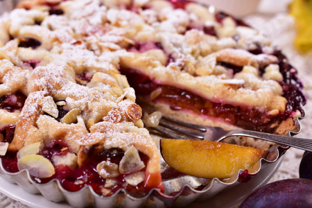 homemade plum tart with crumble and almonds on autumn table