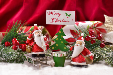 christmas decoration with two funny santa clauses figurine and christmas tree shape card holder with greetings Stock Photo