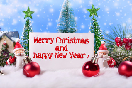 beautiful christmas card with santa clauses figurine in winter scene and greetings text