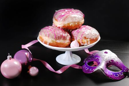 homemade donuts with white and pink icing glaze for carnival party Stock Photo