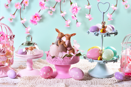 beautiful easter table decoration with painted eggs ,rabbits and flowers in pastel colors  Stock Photo