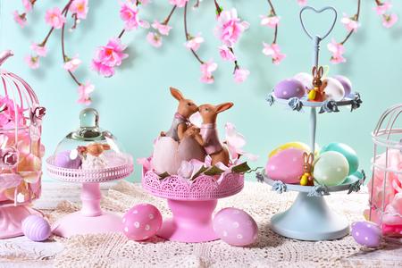 prachtige pasen tafel decoratie met geschilderde eieren, konijnen en bloemen in pastelkleuren Stockfoto