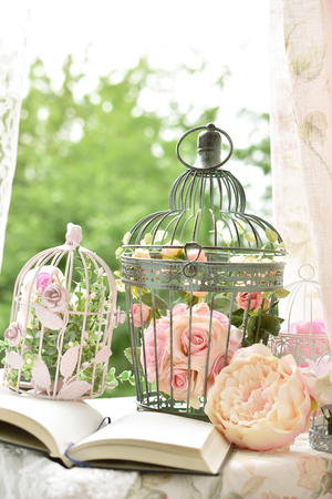 vintage style decoration with opened diary and metal bird cages with flowers on the garden table