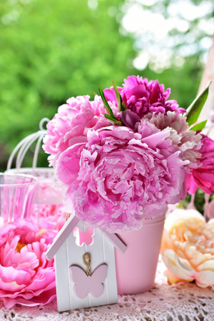 pink peony bunch in vase on the table in the garden Stock Photo