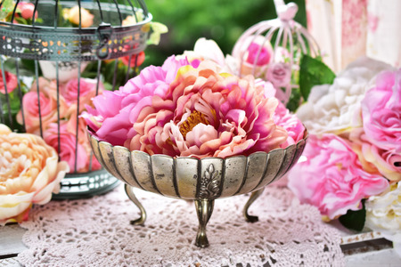 beautiful peony flowers in antique silver bowl and decorations in the garden
