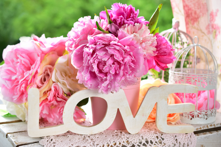 beautiful love decoration with wooden letters and peony flowers on the table in the garden