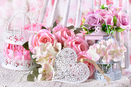 romantic shabby chic love decoration with openwork heart,flowers and bird cages in pastel colors