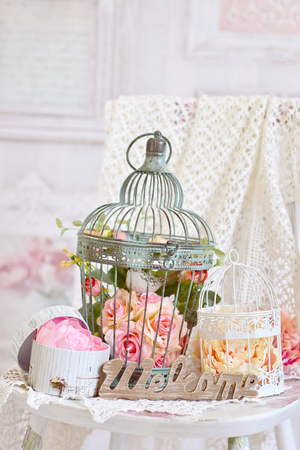 vintage style decoration with flowers in old metal bird cages and wooden letters WELCOME on the chair