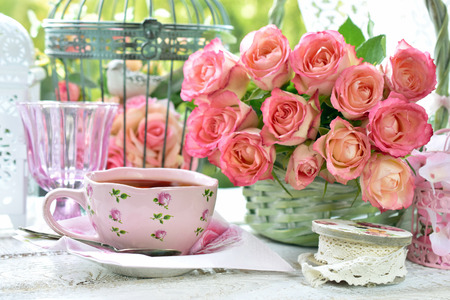 shabby chic style pink cup of tea on the table with bunch of roses and vintage bird cages in the garden Banco de Imagens