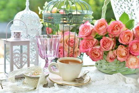Taza de café en la mesa con ramo de rosas y jaulas de pájaros de época en el jardín Foto de archivo - 85942000