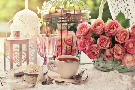 cup of coffee in the morning on the table with bunch of roses and vintage bird cages in the garden
