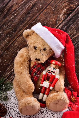 christmas teddy bear in santa hat with vintage nutcracker sitting against wooden background