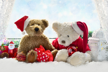two cute teddy bears in santa hats sitting on the window sill and waiting for christmas time