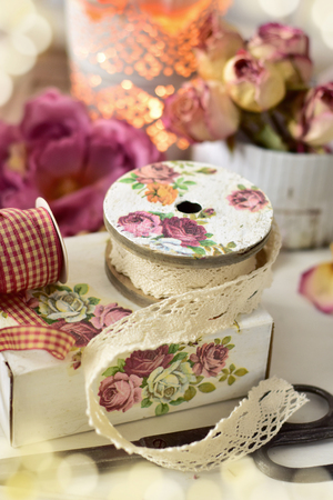 shabby chic style home decoration with bunch of dried roses,old ribbon and lace trim
