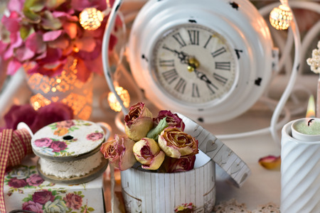 shabby chic style home decoration with old clock ,bunch of dried roses and lace trim Stock Photo