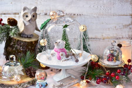 retro style christmas decorations with snowy winter scene with bear and skis closed in big glass dome and sledging boy in smaller one standing on old commode Stock Photo