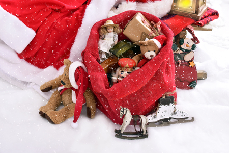 retro style toys as christmas presents in red santa sack lying on the snow outdoor
