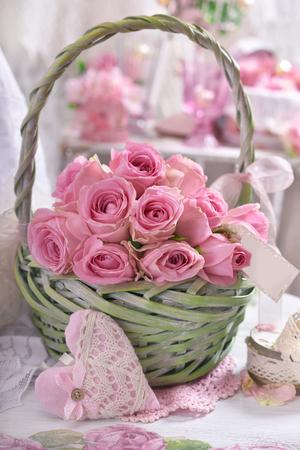 Manojo romántico de rosas rosadas con etiqueta de papel en cesta de mimbre verde en estilo shabby chic interior Foto de archivo - 96157712
