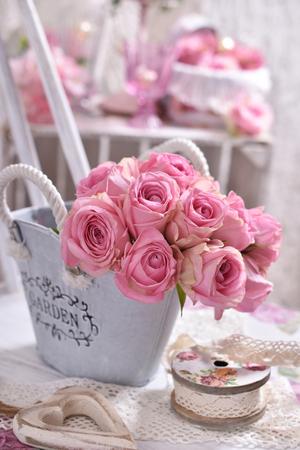 Shabby Chic Stil Innendekoration mit Blumenstrauß von rosa Rosen auf dem Stuhl
