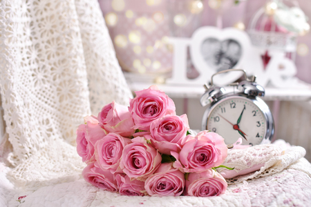 romantic bunch of pink roses lying on the bed,retro alarm clock and love decoration in shabby chic style interior