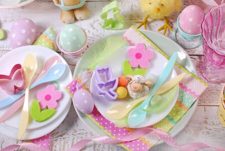 top view of Easter table setting for kids with decorations in pastel colors