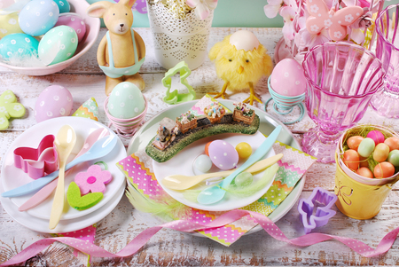 Easter table setting for kids with decorations in pastel colors