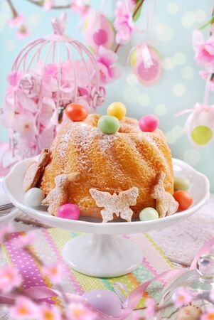 easter ring cake with colorful candy eggs and cookie decoration on festive table in pastel colors