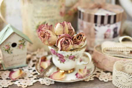 beautiful dried roses in vintage style porcelain cup  with shallow focus 스톡 콘텐츠