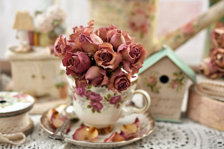 beautiful dried roses in vintage style porcelain cup  with shallow focus Stockfoto