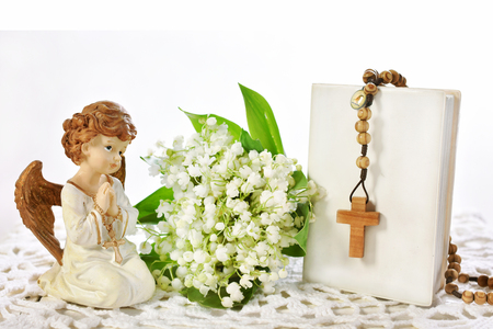 First Holy Communion still life with angel figurine,wooden rosary hanging on prayer book and bunch of lily of the valley flowers isolated on white with cope space for text Zdjęcie Seryjne