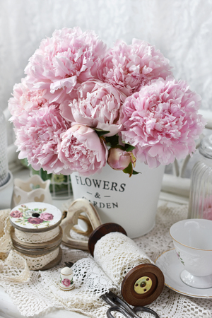 bunch of pink peony flowers in metal bucket in shabby chic style interior