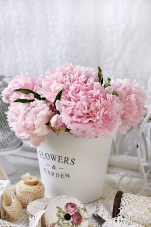 bunch of pink peony flowers in metal basket in shabby chic style interior