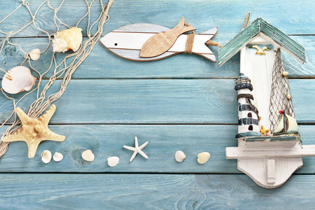 blue wooden background with shells,fishing net and summer souvenirs with empty space for own text