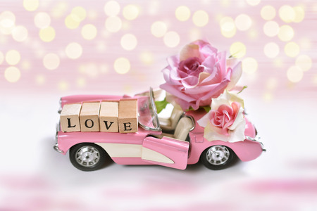 pink cabriolet toy car with roses and wooden cubes with letters LOVE for valentines or wedding card Stock Photo