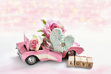 pink cabriolet toy car with heart, roses and wooden cubes with letters LOVE for valentines or wedding card