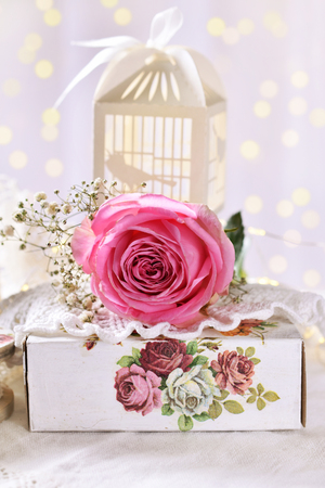 love concept still life with pink rose and paper bird cage box