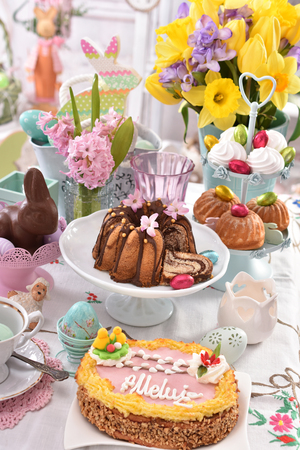 easter festive table with traditional cake called mazurek and ring cake , beautiful decorations and spring flowers Stockfoto - 119887471