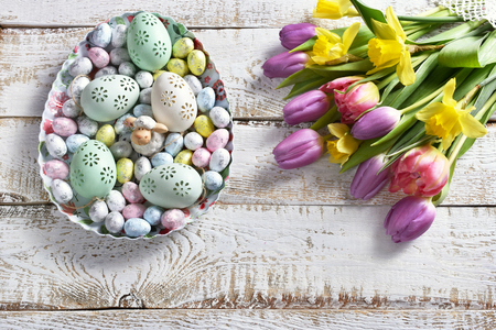easter background with bunch of colorful spring flowers and eggs in egg shaped bowl on white wooden background