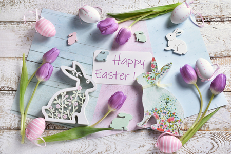 pastel color easter flat lay with purple tulips, eggs and various bunny shape decors and happy easter greeting text