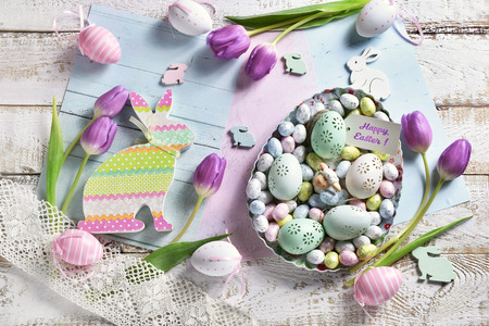 pastel color easter flat lay with purple tulips, eggs in a bowl and a bunny shape decors.Happy easter greetings on paper tag Stockfoto - 119887477