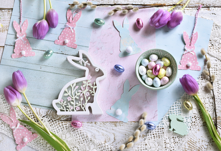 pastel color easter flat lay with purple tulips, bowl with eggs and various bunny shape decors Stockfoto - 119887474