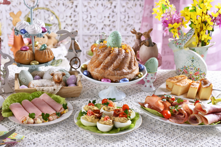 traditional polish easter breakfast with pastries, ham and salad rolls, plater of cold cuts and stuffed eggs on festive table