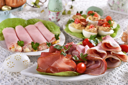 traditional polish easter breakfast with ham and salad rolls, plater of cold cuts and stuffed eggs on festive table Stockfoto