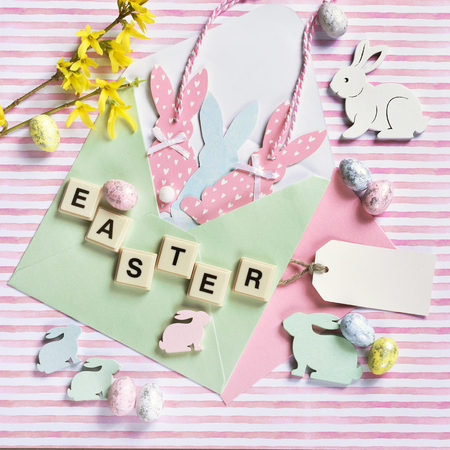 easter flat lay with  bunny decors in envelope, forsythia flowers and letter tiles on striped background