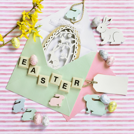easter flat lay with egg shape decor in envelope, bunnies, forsythia flowers and letter tiles on striped background Stockfoto - 119888844